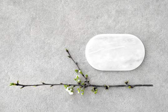 Marble tablet mockup and blooming cherry branch on concrete background.