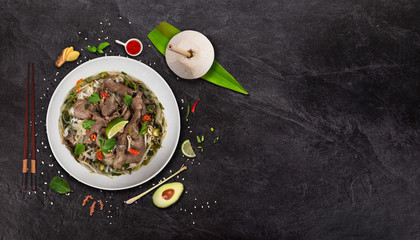 Pho bo asian food background with various ingredients on rustic stone background , top view.