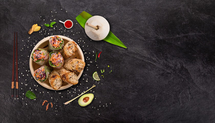 Spring rolls asian food background with various ingredients on stone background.