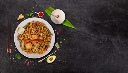 Vegetarian tofu asian food background with various ingredients on rustic stone table.