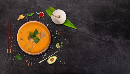 Yellow curry asian food background with various ingredients on stone table.