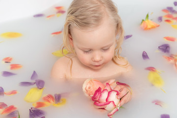 Little girl bathes in a bath with roses