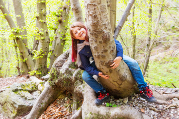 little girl sitting astride a log in a forest