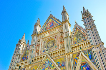 View of the Orvieto Cathedral with beautiful sculptures and painting on the facade in Orvieto, Italy.