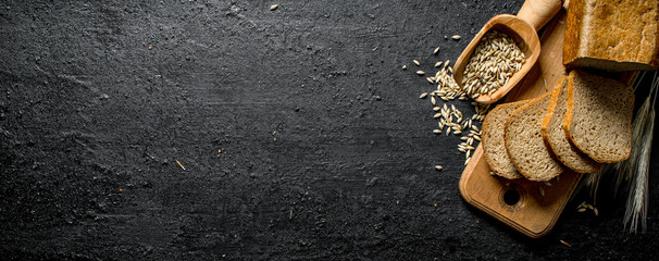 Pieces of bread on a cutting Board with spikelets and grain.