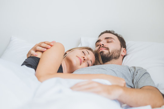 Couple sleeping and hugging happy in white bed