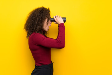 Dominican woman with turtleneck sweater and looking in the distance with binoculars Fotoväggar