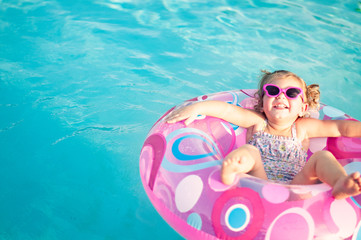 toddler girl floating in swimming pool on an inflatable tube