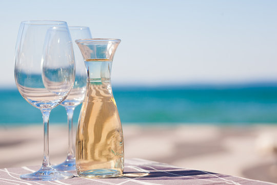 The carafe of white wine and a glass of wine by Garda Lake beach