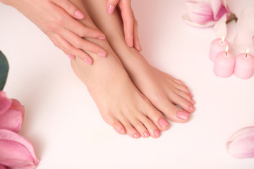 Ideal pedicure and manicure spa shoot. Female legs and hands surrounded by flower flakes.