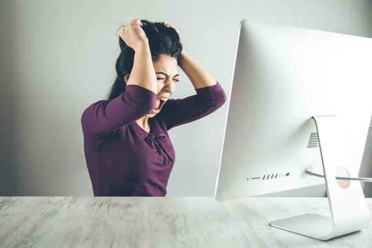 angry woman with computer on desk
