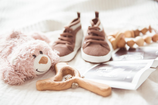Brown booties next to baby photos with ultrasound and other objects of newborns.. The concept of awaiting baby, pregnancy