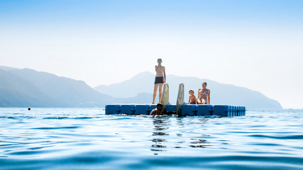 Family swimming and relaxing on floating pontoon at sea