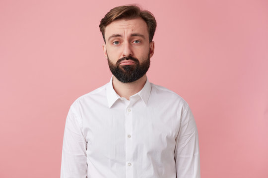 Portrait of a joyless handsome bearded man who was fired from his job. Sadly looking at the camera isolated over pink background.