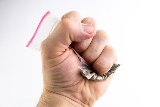 """prohibition of semi-legal smoking mixtures: a bag with synthetic marijuana called """"spice"""" is compressed in a man's fist, on a light background"""