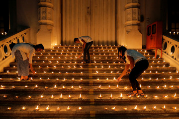 People light candles during a vigil in memory of the victims of a string of suicide bomb attacks across the island on Easter Sunday, in Colombo
