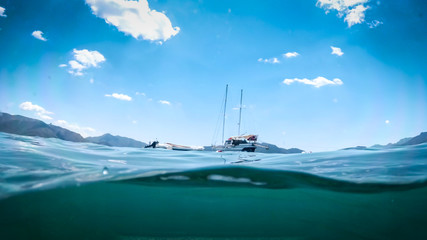 Underwater image of yacht and boat in the sea at bright sunny day