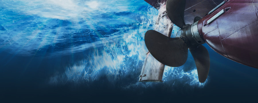 Propeller and rudder of big ship underway view from underwater. Close up image detail of ship. Matte toned.