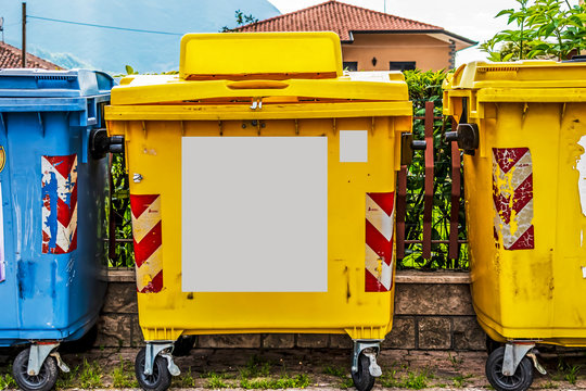 big yellow recycling bin on the street with copy space rectangle
