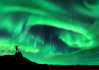 Aurora borealis and silhouette of a man with raised up arms on the mountain peak. Lofoten islands, Norway. Aurora and happy man. Sky with stars and polar lights. Night landscape with aurora and people Fototapete