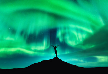 Foto op Plexiglas Noorderlicht Aurora borealis and silhouette of a woman with raised up arms on the mountain peak. Lofoten islands, Norway. Aurora and happy girl. Starry sky and polar lights. Night landscape with aurora and people