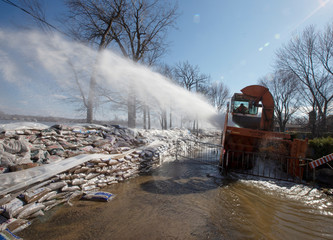 A city snow blower is used to shoot water back into the river from a street in L'Ile-Bizard, a suburb of Montreal, Quebec