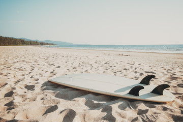 Wall Mural - Surfboard on sand tropical beach with seascape calm sea and sky background. summer vacation background and water sport concept. vintage color tone effect.