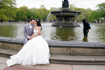 A bride and groom pose for photos as a man takes money out of Bethesda Fountain in Central Park in New York