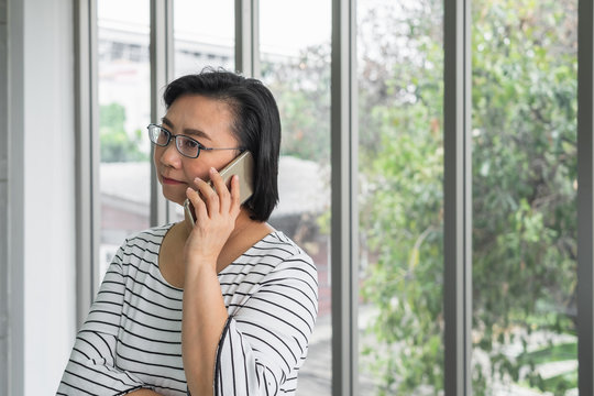 An old Asian woman mother holding a phone in front of a window looking concern and serious.