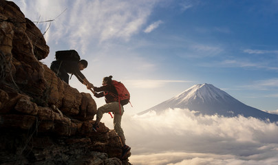Group of Asia hiking help each other silhouette in mountains with sunlight..