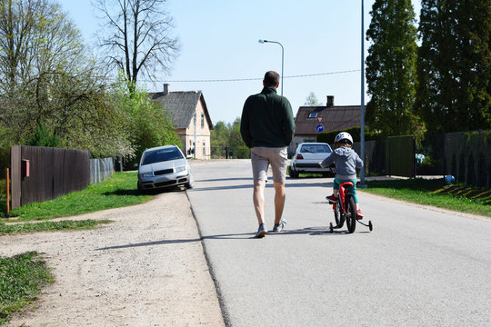Boy in safety helmet cicling first bike on road in spring day, father learning little son to ride with bicycle on street, back view. Happy child making sports. Active leisure activities for children.
