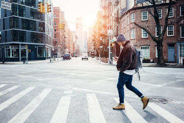 Man wearing hat and jacket walking on the city crossroad with mobile phone in hand Fotomurales