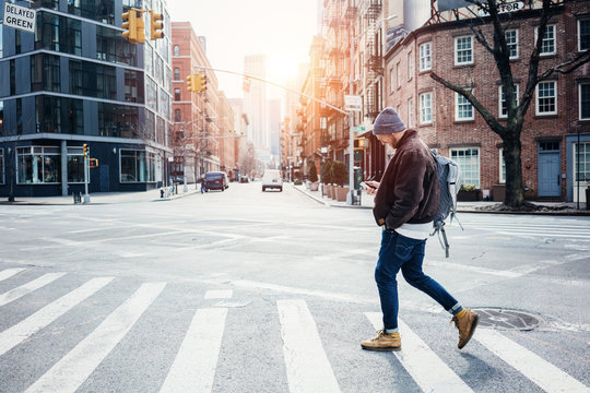 Man wearing hat and jacket walking on the city crossroad with mobile phone in hand