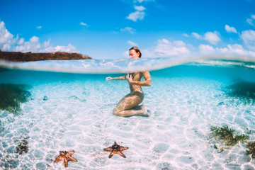 Naked woman swim in blue ocean with starfish, underwater in tropical sea Wall mural