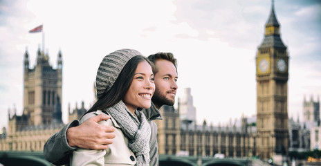 Happy couple by Big Ben Parliament, River Thames, London. Romantic young couple enjoying view during travel. Asian woman, Caucasian man in London, England, United Kingdom. Wall mural
