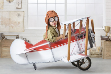 Little boy in the guise of a pilot at the helm of a toy-airplane