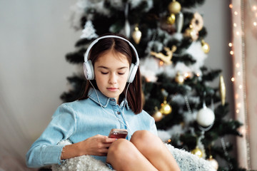 Pretty child girl using headphone for listen music by smartphone on the decorated bedroom with a Christmas tree