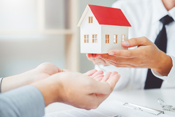 Sale agent giving house to customer and sign agreement contract, Insurance Home concept