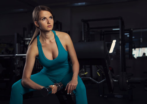 young sport woman sit  in dark gym with dumbbell