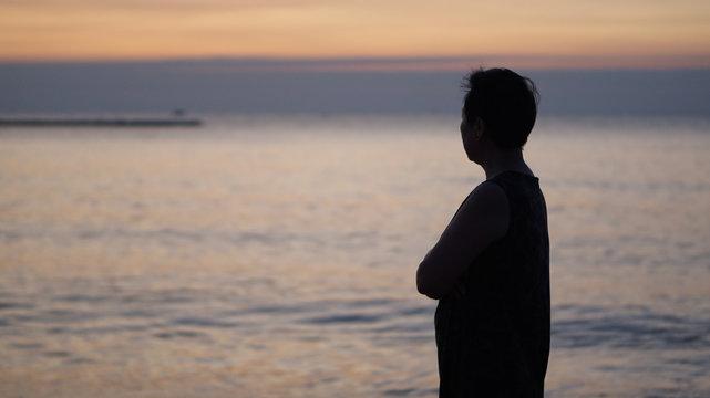 Asian senior woman stand along thinking at sunrise sea silhouette