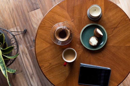 A top down shot of modern living room coffee table with a coffee cup, book, tablet, and a muffin on it.