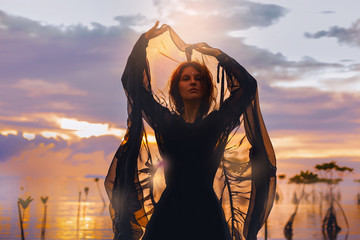 young woman standing in water at sunset silhouette