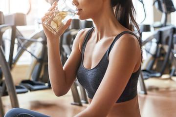 I need water. Cropped photo of beautiful and happy young woman in sports clothing drinking water with lemon while sitting on a mat at gym