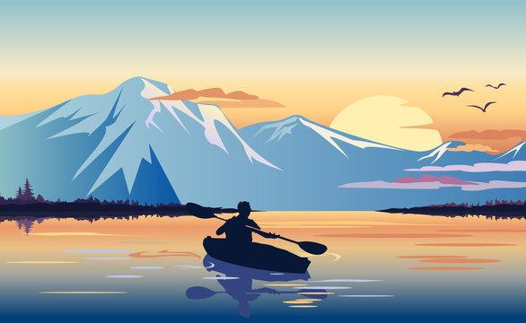 Kayaking in the mountain lake at sunset