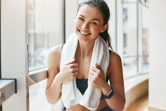 Relaxing. Portrait of happy cheerful woman in sportswear with white towel on her shoulders looking at camera with smile while standing in front of windows at gym