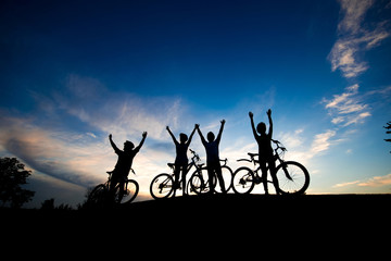 Four cyclists with raised hands at sunset. Group of friends with bicycles standing on meadow at evening sky background. Life is freedom.