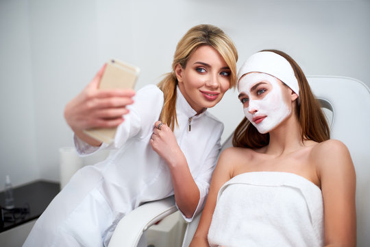 Beautician blogger making selfie with client after applying facial mask for healthy skin. Attractive women making photos with smartphone and relaxing enjoying skincare spa procedures in beauty salon.