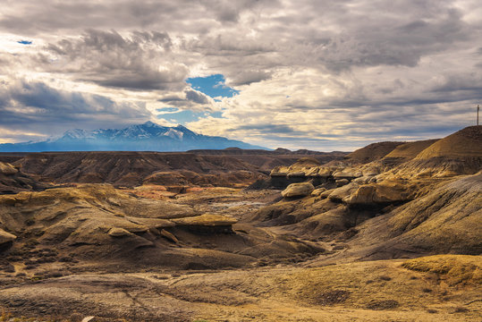 Badlands in Utah with snowy mountains