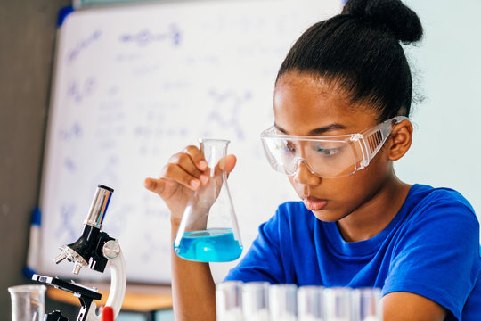 Young African American mixed kid testing chemistry lab experiment and shaking glass tube flask along with microscope - science and education concept