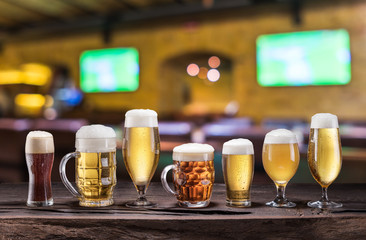 Wall Mural - Cold mugs and glasses of beer on the old wooden table. Blurred pub interior at the background. Assortment of beer.